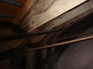 Over den nordre korsarm har tagkonstruktionens krydsbånd fået enderne udskåret med kunstfærdige profiler. På eksemplaret her ses yderligere et tømmermærke dannet af romertal.
